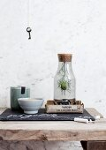 Nigella seed head in bottle with cork stopper in box next to bowl and ceramic storage jar on rustic wooden surface; vintage key hanging on marble wall in background