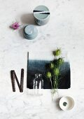 Still-life arrangement of Nigella seed heads on dip-dyed black and white napkin and simple grey china pots on marble surface