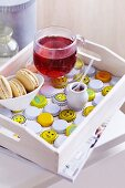 White wooden tray with cup of fruit tea and dish of biscuits arranged on bottle caps painted white and yellow with smiley faces