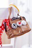 Retro handbag decorated with three bottle tops painted with different motifs