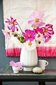 Vase of cosmos in various colours on rustic stool in front of dip-dyed cloth on wall