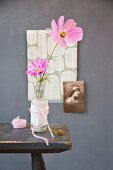 Two delicate cosmos flowers in old glass bottles wrapped in thin paper and matching woollen yarn