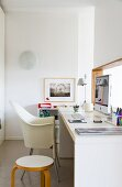 Minimalist, narrow office with white Lord Yo shell chair and yellow-painted wooden stool at modern desk below hatch in wall