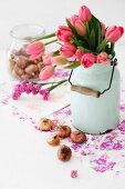 Bouquet of deep pink tulips in nostalgic milk can and bulbs on purple gift wrap