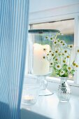 Candle lantern and tealight holders on white windowsill with pale blue striped curtain