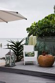 White wicker chair, large floor lantern and drum-shaped side table on terrace made from reclaimed wood and plastic with glass balustrade with sea view
