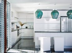 Modern white open-plan kitchen; bulbous metal pendant lamps above counter with white designer cubic bar stools