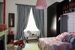 Aeroplane pedal car in faux-antique boy's bedroom; double bed with patchwork covers and headboard integrated into dark blue fitted wardrobe