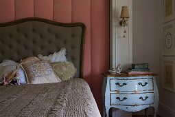 Romantic scatter cushions on bed with button-tufted headboard against wall panel with dusky-pink cover next to pale-blue battered chest of drawers