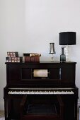 Boxes, antiquarian books and table lamp on top of pianola with music roll