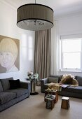 Large portrait of boy, mirrored retro table and brightly coloured coffee table in elegant interior with subdued colour scheme