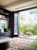View from living room with long-pile rug onto balcony through wide-open glass sliding door