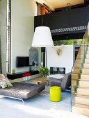 Designer sofa in open-plan, double-height living area with stairs leading to gallery bridge