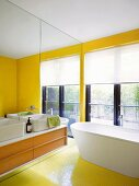 Renovated bathroom with sun-yellow mosaic tiles and washstand with countertop basin on mirrored wall