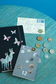 Nostalgically decorated note books, coin collection and old postcard on turquoise surface