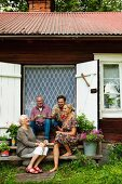 Rustic weekend house - family sitting on wooden steps in front of open door with closed curtain