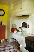 Chimney above old, rustic fireplace and clock on yellow wooden wall in background