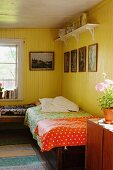 Single bed with colourful bedspread in corner of rustic room painted yellow