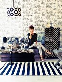 Seating area in fashionable mixture of black and white patterns; woman seated on two-seater sofa, floral wallpaper and striped rug