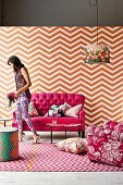 Seating area in feminine shades of pink with antique sofa, wallpaper and rug in zigzag patterns, floral patterned armchair and lampshade and woman wearing mixture of patterns