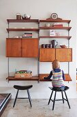 Little girl sitting on wooden stool in front of retro-style, modular shelving system with compartments, cabinets and writing desk on wall-mounted rails