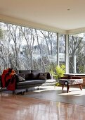 Modern sofa and rustic side table in interior with glass walls and view of trees