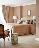 Classic, elegant bedroom in pale beige with antique-style furniture and ceramic stool