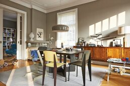Dining room in warm grey with long, wooden sideboard and view into library