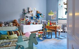 Pastel blue, spacious child's bedroom with cheerful wooden toys and collection of soft toys