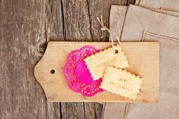 Biscuits and hot pink doily on wooden board; linen napkins on weathered wooden surface