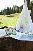 weiße Dessertförmchenen mit verschiedenfarbigem Neon-Rand und Geschirrtuch auf verwittertem Holzblock vor Alm-Landschaft