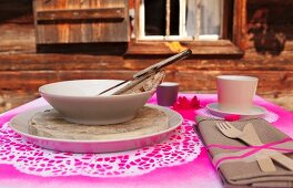 Place setting with soup bowl and wooden cutlery tied to linen napkin on place mat sprayed hot pink through doily stencils in front of alpine cabin