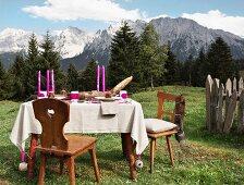 Pinkfarbene Kerzen auf Tisch mit Leinen Tischdecke und rustikalem Flair vor sommerlicher Berglandschaft