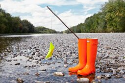Yellow paper boat hanging from hand-made fishing rod stuck in bright orange wellingtons