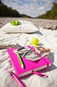 Notizbuch mit pinkfarbenem Einband und knallig gelber Tennisball auf naturfarbener Strickdecke im Freien