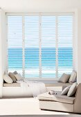 Armchairs in front of window with window seat, open glass louvres and sea view