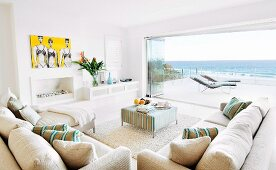 Ecru sofa and ottoman in front of open folding terrace doors in spacious lounge with panoramic sea view