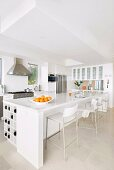 White glossy counter and designer bar stools in open-plan kitchen