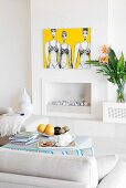 Afternoon break - cups, teapot and fruit bowl on ottoman opposite open fireplace below contemporary artwork on wall