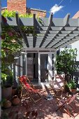 Deckchairs on sunny terrace below grey wooden lattice pergola adjoining house with open door