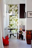 Young child sitting on child's chair in kitchen, retro chair at round table and floor-to-ceiling patterned curtain