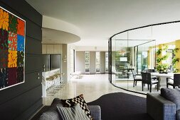 Lounge area with black wall in front of light-flooded dining area behind curved glass partition in spacious modern interior