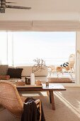 Wicker armchair, pale sofa, rustic coffee table and panoramic window in bright, pleasant living room