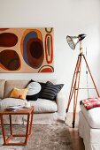 Studio lamp on old wooden tripod next to seating area with simple coffee table and modern artwork on wall