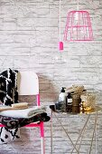 Toiletries on chrome side table next to stacked towels on chair against stone-effect wallpaper and below pendant lamp with pink wire lampshade