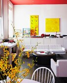 Lounge area with round coffee table and white sofa in front of wall with yellow artworks above sideboard