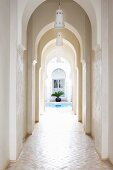 Narrow arcade in entrance area of Moroccan house with view of pool and palm trees in courtyard