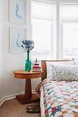 Schlafzimmer mit Bett, Patchworkdecke & Nachttisch mit runder Holzplatte vor Erkerfenster