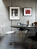 Various Bauhaus chairs at round table in front of framed pictures on grey wall panels