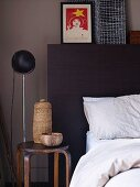Partially visible bed with dark headboard next to rustic vessels on simple stool and standard lamp against grey wall